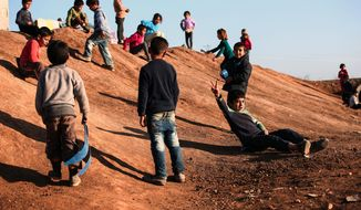 Syrian refugee children who fled violence in Syrian city of Ain al-Arab, known also as Kobani, play outside their tents in a camp in the border town of Suruc, Turkey, Sunday, Feb. 1, 2015. About 200,000 people arrived in Turkey since the start of fighting between Kurdish militia and Islamic State militants mid-September, 2014.(AP Photo/Emrah Gurel)