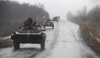 Ukranian military vehicles are seen driving on the road towards the town of Artemivsk, Ukraine, Sunday, Feb. 1, 2015. Fighting between government and Russian-backed separatist forces in eastern Ukraine has intensified in recent days as rebels seek to encircle the town of Debaltseve, which hosts a strategically important railyway hub. (AP Photo/Petr David Josek)