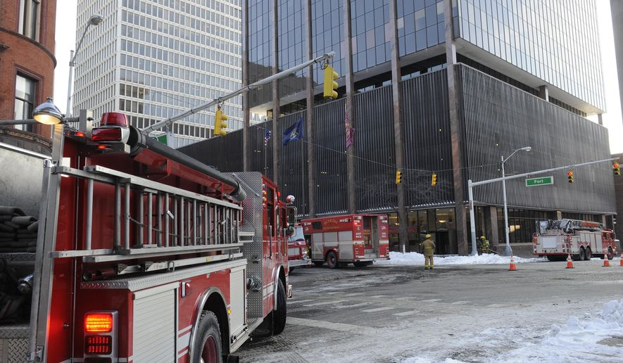Detroit Fire Department respond to an explosion at the Fort Washington Plaza in Detroit on Tuesday, Feb. 3, 2015.  Officials say an underground electrical problem sent three manhole covers into the air in downtown, prompting the evacuation of an office building. No injuries are reported. (AP Photo/Detroit News, David Coates)  DETROIT FREE PRESS OUT; HUFFINGTON POST OUT