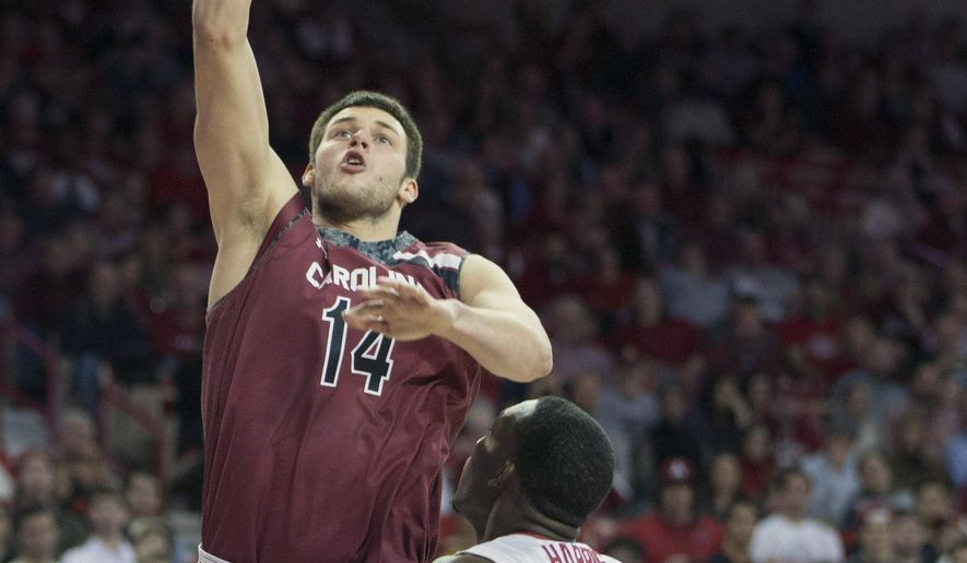 South Carolina forward Laimonas Chatkevicius, left, shoots a one handed layup over Arkansas forward Alandise Harris, right, during the first half of an NCAA college basketball game on Tuesday, Feb. 3, 2015, in Fayetteville, Ark. (AP Photo/Gareth Patterson)