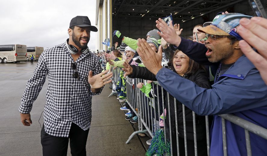 Seattle Seahawks quarterback Russell Wilson greets airline employees and their families on the team's return from the Super Bowl Monday, Feb. 2, 2015, at Seattle-Tacoma International Airport in SeaTac, Wash. The Seahawks lost in the Super Bowl to the New England Patriots on Sunday. (AP Photo/Elaine Thompson)