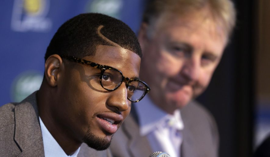 FILE - In this Sept. 25, 2013, file photo, Indiana Pacers forward Paul George, left, talks about signing a multi-year contract extension with the NBA basketball team as team president Larry Bird looks on during a news conference in Indianapolis. Bird said, Tuesday, Feb. 3, 2015, that he hopes George can return to the game this season after breaking his leg in a gruesome accident last summer, perhaps as soon as next month. (AP Photo/Michael Conroy, File)