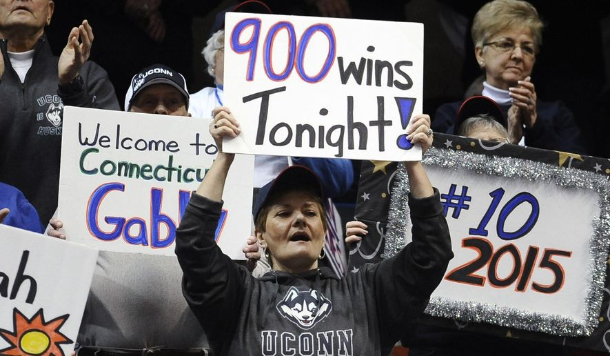 Connecticut fans hold up signs during the first half of an NCAA college basketball game between UConn and Cincinnati, Tuesday, Feb. 3, 2015, in Hartford, Conn.  Connecticut coach Geno Auriemma had 899 career wins going into the game.  (AP Photo/Jessica Hill)