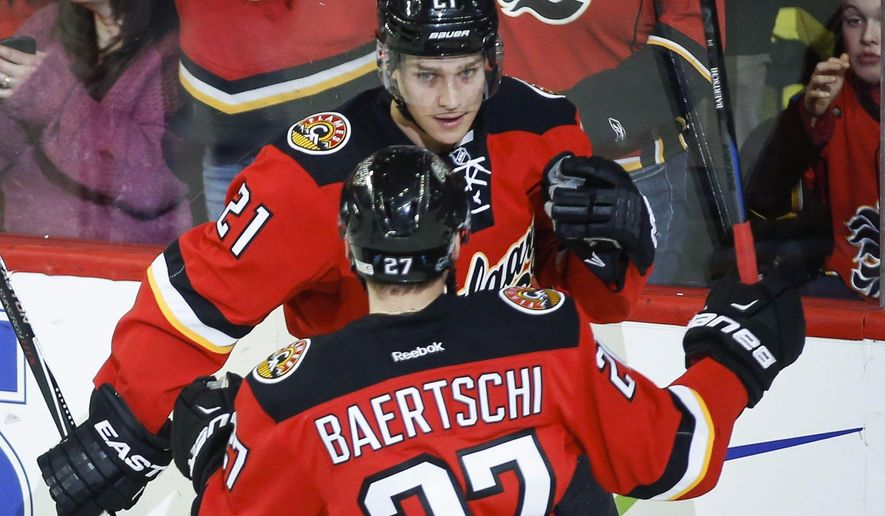 Calgary Flames Mason Raymond, right, celebrates his goal with teammate Sven Baertschi, from Switzerland, during second period of an NHL hockey game in Calgary, Alberta, Monday, Feb. 2, 2015. (AP Photo/The Canadian Press, Jeff McIntosh)