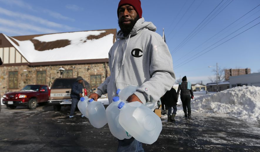 Lemott Thomas carries free water being distributed at the Lincoln Park United Methodist Church in Flint, Mich., Tuesday, Feb. 3, 2015. The city gets tap water from the Flint River, but residents have complained about the smell, taste and appearance. The city says the water is safe to drink. The federal government, however, has cited Flint for high levels of a disinfectant byproduct.  (AP Photo/Paul Sancya)