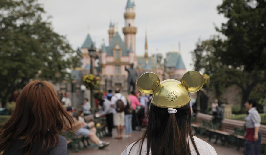 FILE - In this Jan. 22, 2015, file photo, a woman with a Mickey Mouse hat walks toward Sleeping Beauty's Castle at Disneyland, in Anaheim, Calif. Disney reported another quarter of strong growth on Tuesday, Feb. 3, helped by higher revenue from its parks and resorts. Walt Disney Co. CEO Bob Iger says the measles outbreak is having no discernible impact on attendance at its parks and resorts. (AP Photo/Jae C. Hong, File)