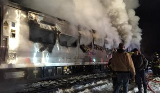 A Metro-North Railroad passenger train smolders after hitting a vehicle in Valhalla, N.Y., Tuesday, Feb. 3, 2015. (AP Photo/The Journal News, Frank Becerra Jr)