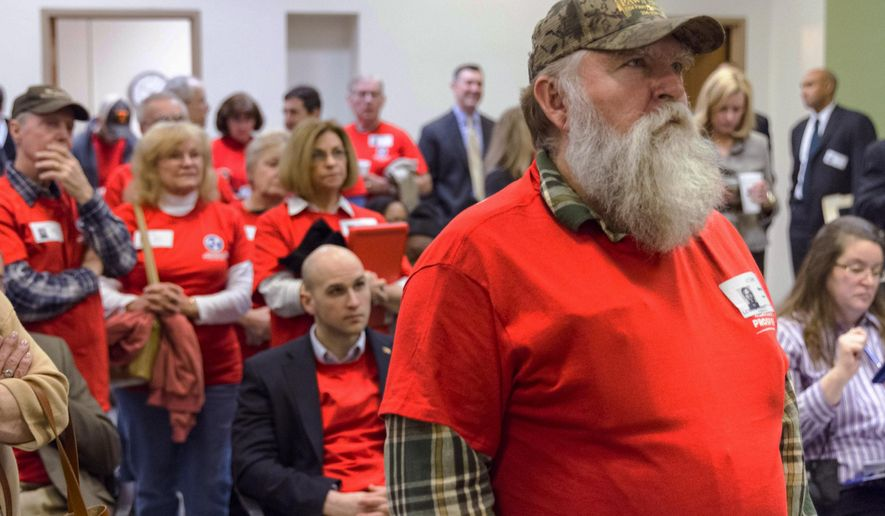 David Jones of Lawrenceburg, Tenn., and other opponents of Gov. Bill Haslam's Insure Tennessee proposal watch a committee hearing on a television in the legislative office complex in Nashville, Tenn., on Tuesday, Feb. 3, 2015. Haslam has said the program would cover 280,000 low-income Tennesseans using money available under President Barack Obama's health care law. (AP Photo/Erik Schelzig)
