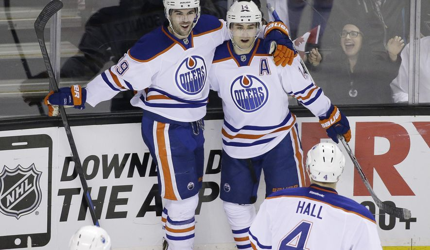 Edmonton Oilers right wing Jordan Eberle (14) is greeted by teammates Justin Schultz (19) and Taylor Hall (4) after scoring a goal during the first period of their NHL hockey game against the San Jose Sharks Monday, Feb. 2, 2015, in San Jose, Calif. (AP Photo/Eric Risberg)