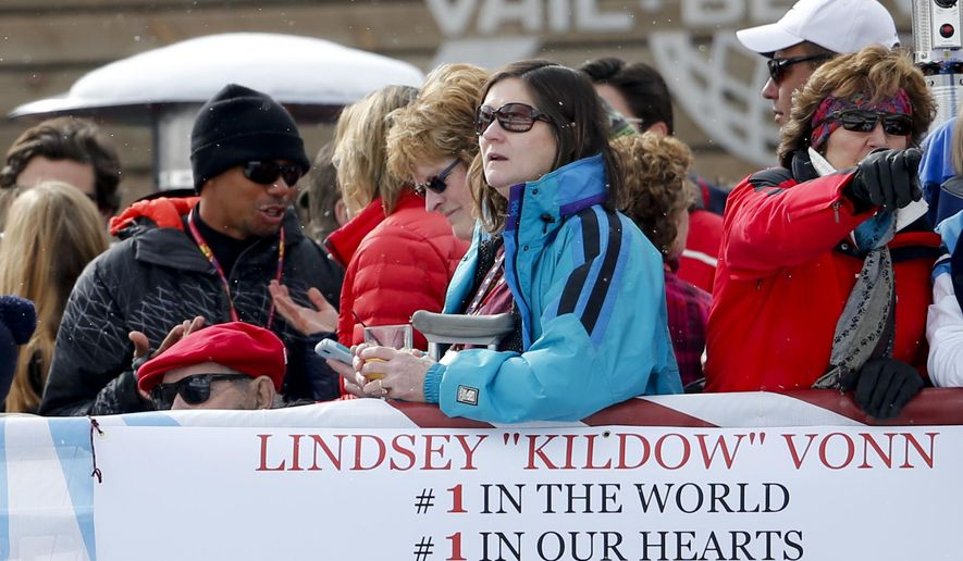 Tiger Woods, left, talks with supporters of his  girlfriend  Lindsey Vonn, of the United States, as she competes in the women's super-G race at the alpine skiing world championships on Tuesday, Feb. 3, 2015, in Beaver Creek, Colo.(AP Photo/Marco Trovati)