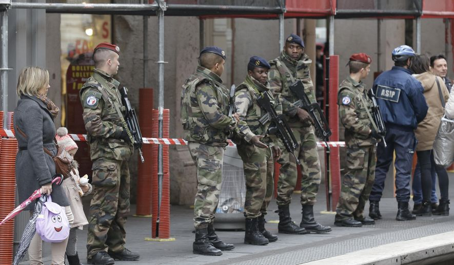 Soldiers stand guard after an attacker with a knife hidden in his bag attacked three soldiers on an anti-terror patrol in front of a Jewish community center in Nice, southern France, Tuesday Feb.3, 2015 . France has been on high alert since the attacks in the Paris region by three Islamic extremists that left 20 people dead, including the gunmen. More than 10,000 soldiers have been deployed around the country to protect sensitive locations, including major shopping areas, synagogues, mosques and transit hubs. (AP Photo/Lionel Cironneau)