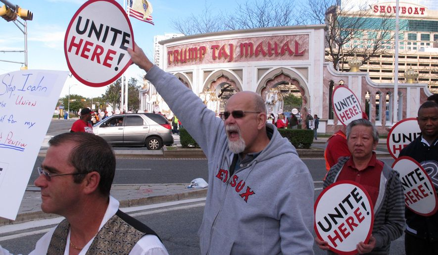 This Oct. 24, 2014 photo shows union members picketing outside the Trump Taj Mahal casino in Atlantic City N.J. On Tuesday Feb. 3, 2015, Local 54 of the Unite-HERE union filed 27 unfair labor practices against Trump Entertainment resorts with the National Labor Relations Board, alleging management threatened workers and unilaterally changed schedules and work rules to hurt workers during a still-unresolved contract dispute. The company declined comment. (AP Photo/Wayne Parry)