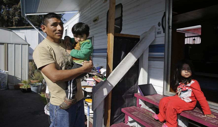 Alex Simangas, a cook at a local pizza restaurant, stands with his son Alex and daughter Teresa outside their home at the Buena Vista Mobile Home Park, Tuesday, Feb. 3, 2015, in Palo Alto, Calif. Silicon Valley's tech economy is continuing to boom, with 58,000 new jobs and 42,000 new residents last year and all indications the record growth will continue, according to study released Tuesday. The report shows that with the income and population growth, low wage earners are being priced out of housing, roadways are increasingly congested, and public rail service is overwhelmed throughout the greater Bay Area. (AP Photo/Eric Risberg)