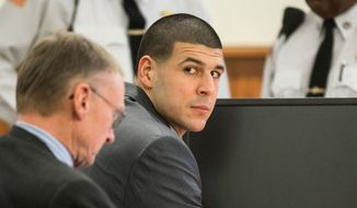 Former New England Patriots player Aaron Hernandez, right, glances towards the Lloyd family during his trial at Bristol County Superior Court in Fall River, Ma., Tuesday, Feb. 3, 2015. Hernandez is accused of the June 2013 killing of Odin Lloyd.  (AP Photo/The Boston Globe, Aram Boghosian, Pool )