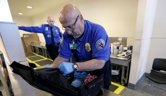 A TSA agent checks a bag at a security checkpoint area at Midway International Airport in Chicago. (Associated Press)