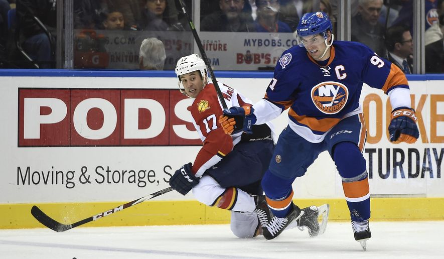 New York Islanders center John Tavares (91) overtakes Florida Panthers center Derek MacKenzie (17) to gain possession of the puck in the second period of an NHL hockey game at Nassau Coliseum on Tuesday, Feb. 3, 2015, in Uniondale, N.Y. (AP Photo/Kathy Kmonicek)