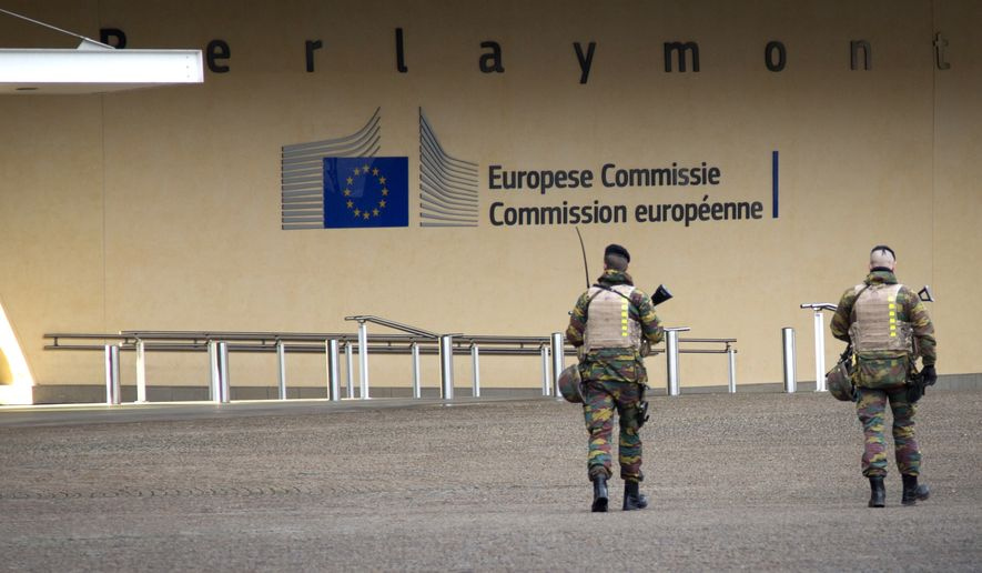 Two Belgian soldiers patrol outside EU headquarters in Brussels on Monday, Feb. 2, 2015. The Belgian Army is patrolling key sites in Belgium as a safety precaution against potential terrorist threats. (AP Photo/Virginia Mayo)