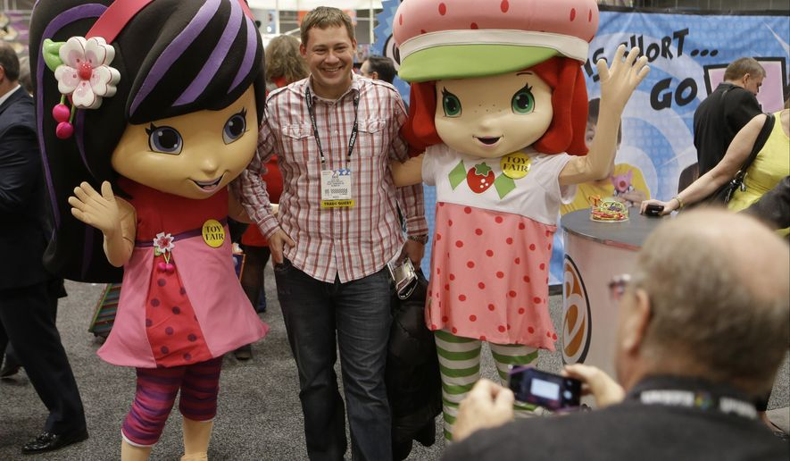"""FILE - IN this Feb. 16, 2014 file photo, characters Strawberry Shortcake, right, and Cherry Jam, left, pose for a photograph with David Yakos at Toy Fair 2014 at the Jacob K. Javits Convention Center  in New York.   Iconix, the brand licensing company that owns the """"Peanuts"""" gang of characters, says it is buying the rights to cartoon character Strawberry Shortcake for $105 million from greeting card company American Greetings. (AP Photo/Frank Franklin II)"""