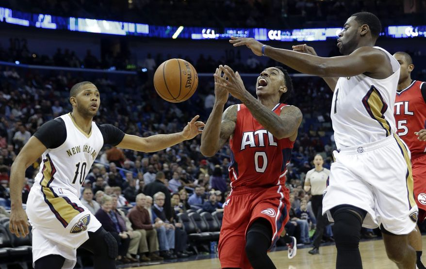 Atlanta Hawks guard Jeff Teague (0) loses the ball as he drives to the basket between New Orleans Pelicans guard Eric Gordon (10) and guard Tyreke Evans (1) in the second half of an NBA basketball game in New Orleans, Monday, Feb. 2, 2015. The Pelicans won 115-100. (AP Photo/Gerald Herbert)