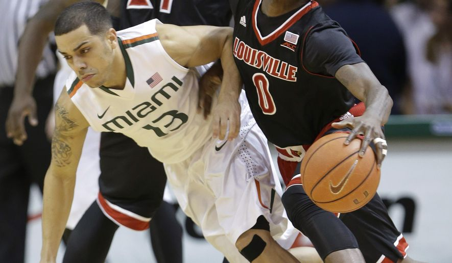Louisville guard Terry Rozier (0) collides with Miami guard Angel Rodriguez (13) during the first half of an NCAA college basketball game, Tuesday, Feb. 3, 2015, in Coral Gables, Fla. (AP Photo/Wilfredo Lee),