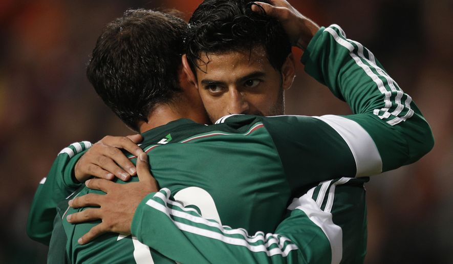 FILE - In this Nov. 12, 2014 file photo, Mexico's Carlos Vela, right, celebrates a goal during an international friendly soccer match with the Netherlands in Amsterdam, Netherlands. Vela, who plays with Real Sociedad, suffered a torn meniscus during a match in Spain with Real Madrid on Saturday, Jan. 31, 2015. (AP Photo/Peter Dejong, File)