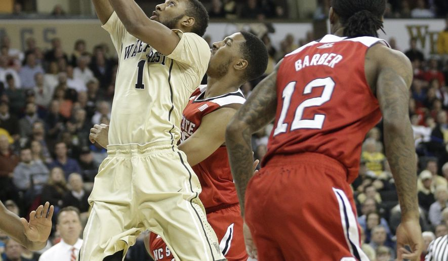 Wake Forest's Madison Jones, left, drives past North Carolina State's Anthony Barber, right, and Ralston Turner, back, during the first half of an NCAA college basketball game in Winston-Salem, N.C., Tuesday, Feb. 3, 2015. (AP Photo/Chuck Burton)