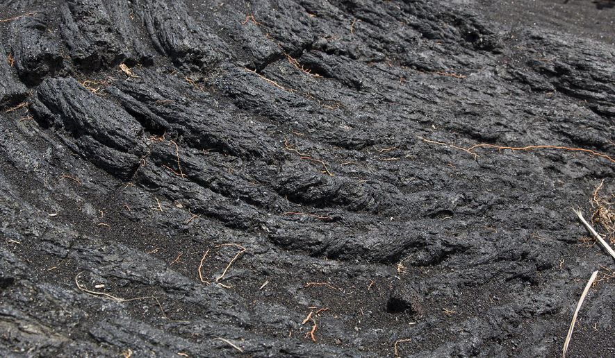 This Aug. 15, 2014 photo shows a lava field near the New Kaimu Beach, in Kalapana, Hawaii. The black sand Kaimu Beach was formed on the eastern shores of the Big Island after lava from the Kilauea volcano engulfed the town of Kalapana in 1990, destroying most of the homes. (AP Photo/Marco Garcia)