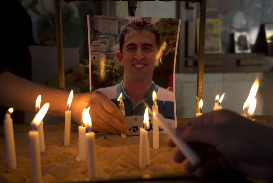 Two Jordanian women light candles next to a picture of Jordanian pilot, Lt. Muath al-Kaseasbeh, who was being held by Islamic State group militants, following Sunday prayers in the Adir Roman Catholic Church, on the outskirts of Karak, Jordan, Sunday, Feb. 1, 2015. (AP Photo/Nasser Nasser)