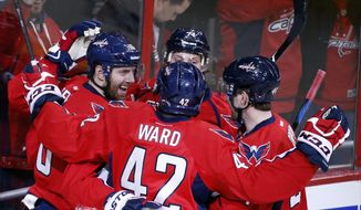 Washington Capitals right wing Eric Fehr, left, smiles as he celebrates with right wing Joel Ward (42) and others, after Fehr's goal during the third period of an NHL hockey game against the Los Angeles Kings, Tuesday, Feb. 3, 2015, in Washington. The Capitals won 4-0. (AP Photo/Alex Brandon)