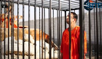 This still image made from video released by Islamic State group militants and posted on the website of the SITE Intelligence Group on Tuesday, Feb. 3, 2015, purportedly shows Jordanian pilot Lt. Muath al-Kaseasbeh standing in a cage just before being burned to death by his captors. The death of the 26-year-old pilot, who fell into the hands of the militants in December when his Jordanian F-16 crashed near Raqqa, Syria, followed a weeklong drama over a possible prisoner exchange. (AP Photo/SITE Intelligence Group)