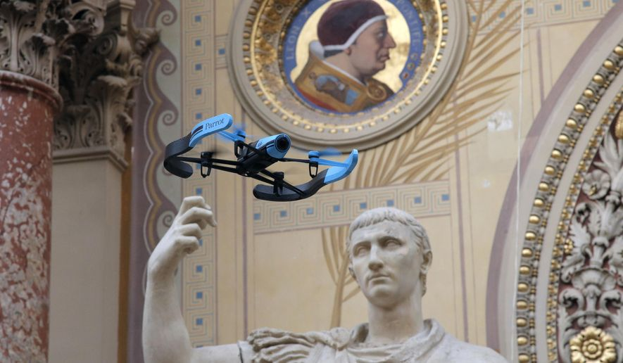 """FILE - In this Nov. 7, 2014 file photo, the new Bebop Parrot drone flies past a Rome marble statue """"August en Triomphateur"""" during a presentation to the press in Paris, France. Befuddled by a spate of small mystery drones flying over its nuclear plants, military installations, and even the presidential palace, France has asked its scientific minds to help devise a way to counteract small _ and so far harmless _ motorized menaces overhead. (AP Photo/Francois Mori, File)"""
