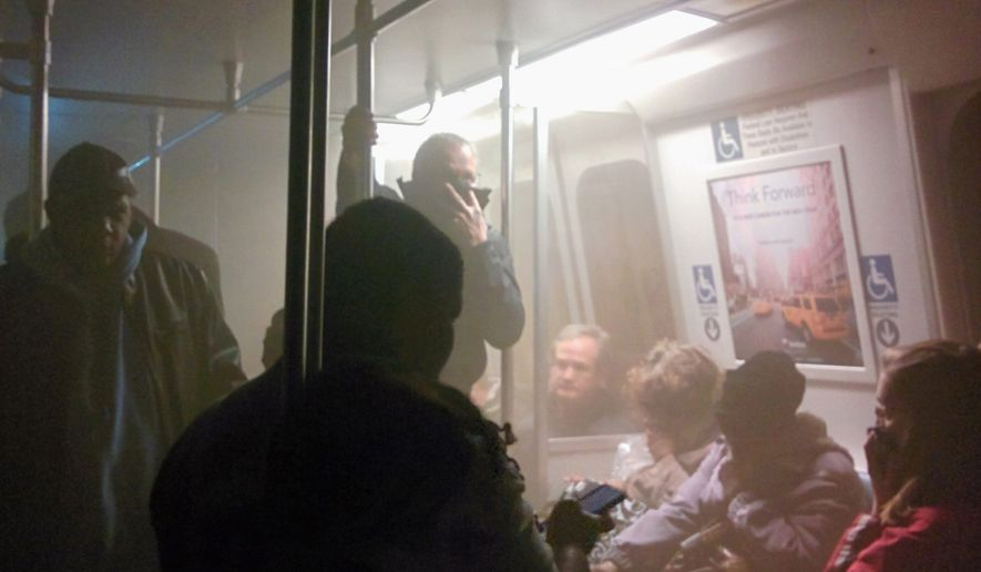 A passenger who was injured in the Jan. 12 Metro fire claims that three transit officers saw smoke coming from the tunnel and went to investigate before the train became disabled. (Associated Press)