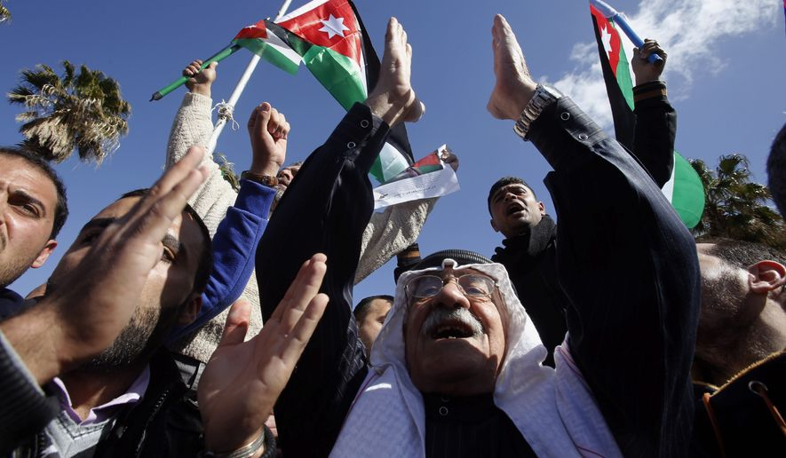 Jordanians chant slogans to show their support for the government against terror as they were waiting for Jordan's King Abdullah II, returning from the U.S., at Queen Alia Airport in Amman, Wednesday. King Abdullah II rushed home Wednesday, cutting short a U.S. trip, to rally public support for even tougher strikes against the Islamic State group after the militants released a video showing the captured Jordanian pilot being burned to death in a cage. (Associated Press)