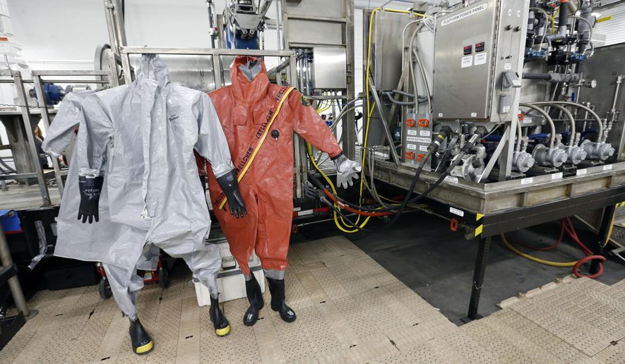 In this Jan. 29, 2015 photo, protective suits for workers used in chemical munitions destruction hang inside the Pueblo Chemical Depot, east of Pueblo, in southern Colorado. The United States is about to begin destroying its largest remaining stockpile of chemical-laden artillery shells, a milestone in the global campaign to eradicate a debilitating weapon that still creeps into modern wars. (AP Photo/Brennan Linsley)