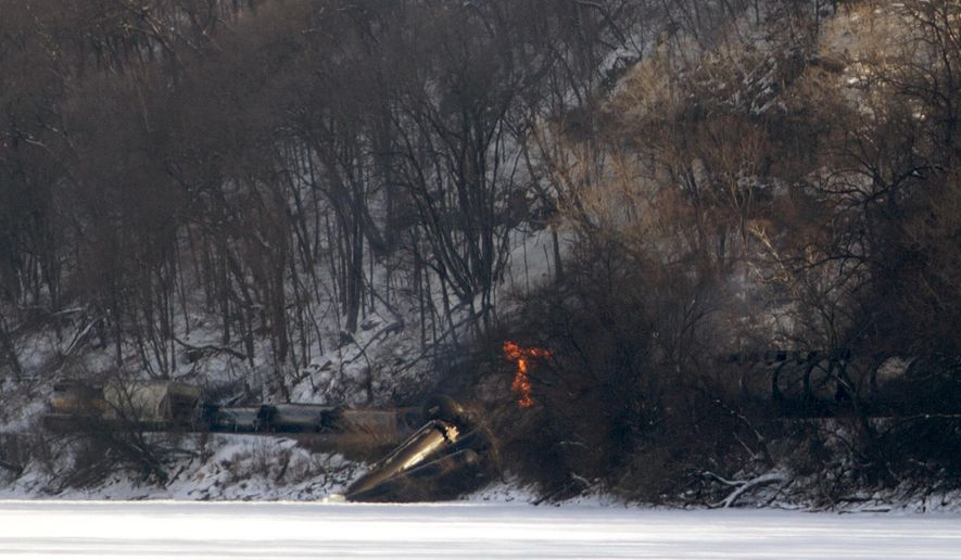 Iowa Department of Natural Resources staff are on the scene of a train derailment in which three railcars caught fire and another three plunged into the Mississippi River. In all, 11 cars derailed, and 10 of them were carrying ethanol, north of Dubuque, Iowa, on Wednesday, Feb. 4, 2015. (AP Photo/Dubuque Telegraph Herald, Mike Burley)