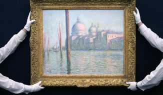 "In this Wednesday, Jan. 28, 2015, file photo, Sotheby's staff pose for a picture with ""Le Grand Canal"" by Claude Monet, during a preview of their upcoming Impressionist and Modern, Surrealist and Contemporary Art sale, at the auction house in London, England. (AP Photo/Tim Ireland, File)"