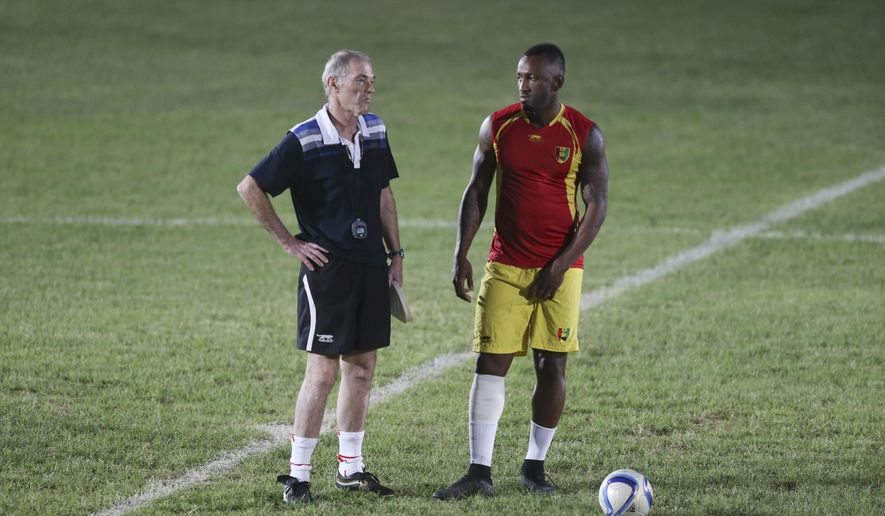 Guinea national soccer team coach, Michel Dussuyer, left, speaks to player Kamil Zayatte, right,  during a training session at the Estadio De La Paz ahead of their quarterfinal match against Ghana, at Estadio De Malabo in Malabo, Equatorial Guinea, Friday, Jan. 30, 2015. (AP Photo/Sunday Alamba)