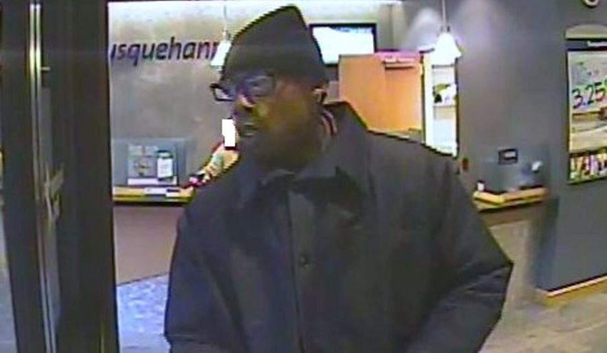 This image taken from video provided by the Federal Bureau of Investigation shows a man who authorities say robbed a Susquehanna Bank branch with a fake grenade on Tuesday, Feb. 3, 2015 in Philadelphia. The man, wearing a black knit hat and a dark coat, took an undisclosed amount of cash and fled on foot. Police found the device about half-mile away and the bomb squad determined the grenade was just a replica. (AP Photo/Federal Bureau of Investigation)