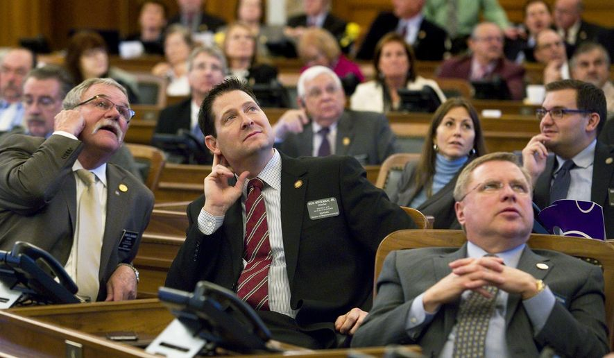 Members of the Kansas House, including House Appropriations Chairman Rep. Ron Ryckman Jr., R-Olathe, center,  watch the vote boards Wednesday, Feb. 4, 2015,  as the House gave its final approval to a measure intended to keep the state afloat financially. The legislation now heads to the Senate, where it must be passed in less than 10 days to stop a fiscal crisis. Ryckman carried the bill on the floor. (AP Photo, Topeka Capital-Journal, Thad Allton)