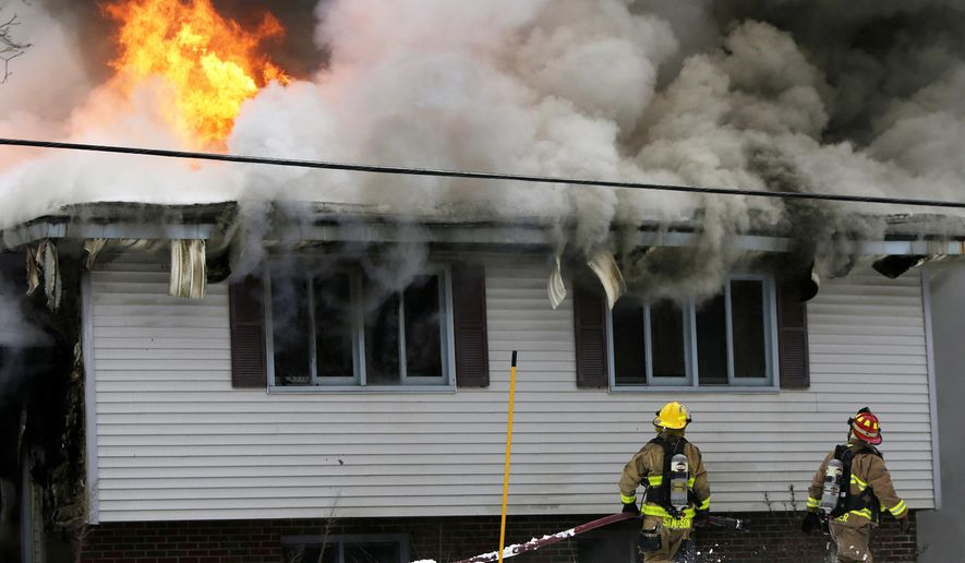 In this photo taken on Tuesday, Feb. 3, 2015, firefighters work to put out a fire at a home in Holton, Mich. One man perished in the house fire. The fire likely was caused by a wood stove according to Holton Fire Chief Art Stevens. (AP Photo/The Muskegon Chronicle, Tommy Martino ) ALL LOCAL TELEVISION OUT; LOCAL TELEVISION INTERNET OUT