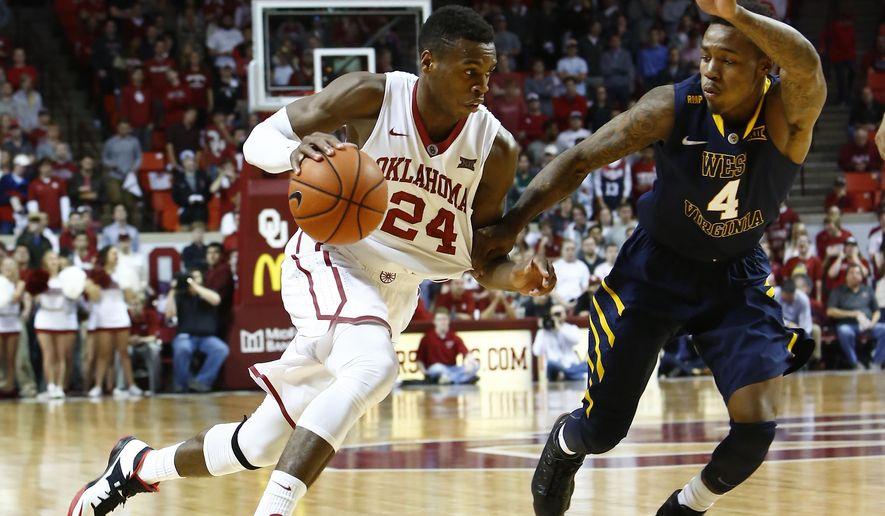 Oklahoma guard Buddy Hield (24) drives to the basket as West Virginia guard Daxter Miles Jr. (4) defends during the second half of an NCAA college basketball game in Norman, Okla., Tuesday, Feb. 3, 2015. Oklahoma won 71-52. (AP Photo/Alonzo Adams)