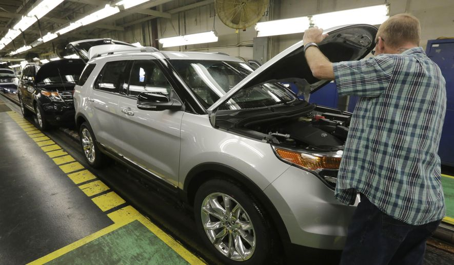 FILE - In this Oct. 22, 2014 photo, workers perform final inspections on 2015 Ford Explorers on the assembly line at the Chicago Ford Assembly Plant. Ford Motor Co. on Wednesday, Feb. 4, 2015 said it is moving several hundred U.S. hourly workers into a higher pay bracket after surpassing a cap on the number of lower-wage workers it can hire. (AP Photo/M. Spencer Green, File)