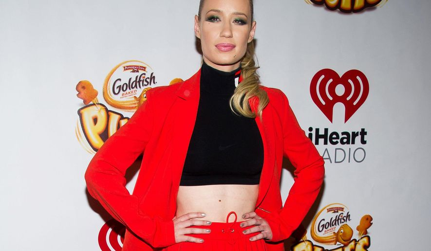 FILE - In this Dec. 12, 2014 file photo, Iggy Azalea poses in the Z100 Jingle Ball press room at Madison Square Garden in New York. Azalea was nominated for five iHeartRadio Music Awards, including artist of the year on Wednesday, Feb. 4, 2015. The awards will be presented March 29 at the Shrine Auditorium in Los Angeles. The event will be televised live on NBC and air simultaneously on iHeartMedia stations and across the network's digital music platform. (Photo by Charles Sykes/Invision/AP, File)