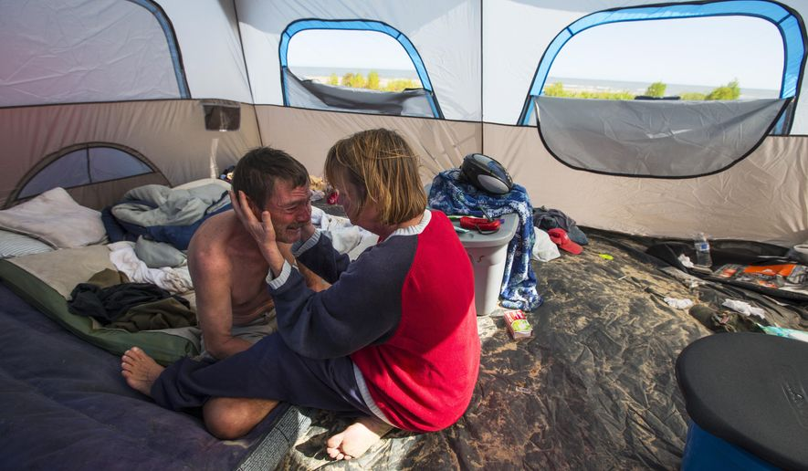 Kevin Kurtz and Darcy Robertson sit in their tent on the beach Thursday, Jan. 29, 2015, on the Bolivar Peninsula in Texas.  Kurtz, 51, and Robertson, 54, were surprised to learn that camps such as theirs are among the reasons Galveston County is seeking legislative authority to regulate peninsula beaches.  They say they have kept out of trouble and pride themselves in the cleanliness of their encampment, but complaints about long-term campers over the years led commissioners to seek the new authority.  (AP Photo/Houston Chronicle, Brett Coomer)   MANDATORY CREDIT