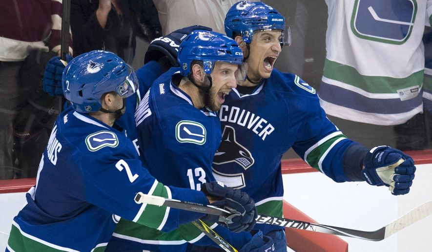 Vancouver Canucks defenseman Luca Sbisa (5) celebrates his game-winning goal with teammates Nick Bonino (13) an Dan Hamhuis (2) during overtime of an NHL hockey game against the Winnipeg Jets on Tuesday, Feb. 3, 2015, in Vancouver, British Columbia. Vancouver won 3-2. (AP Photo/The Canadian Press, Jonathan Hayward)