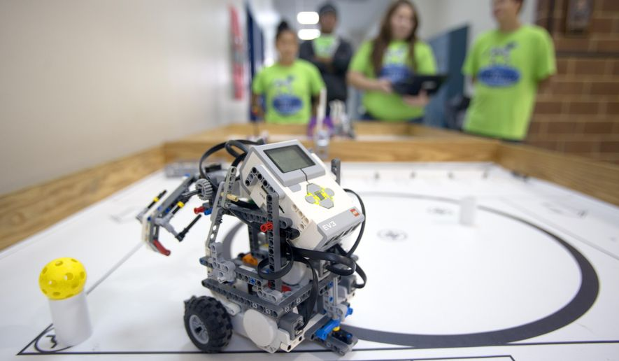 A TCEA (Texas Computer Education Association) style robot performs tasks Thursday Jan. 29, 2015 in a TCEA arena as members of the Natalia High School robotics team watch in Natalia, Texas.  Natalia High School, which has 315 students, will send three teams, and possibly a fourth, to the TCEA, or Texas Computer Education Association, state robotics championship in May based on scores from the regional contest in Alamo Heights last month. It will mark the seventh straight year that Natalia has been represented at the TCEA championship.  (AP Photo/The San Antonio Express-News, William Luther)  RUMBO DE SAN ANTONIO OUT; NO SALES