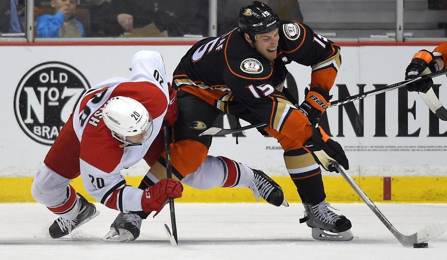 Carolina Hurricanes center Riley Nash, left, and Anaheim Ducks center Ryan Getzlaf competes for the puck after a face-off during the first period of an NHL hockey game, Tuesday, Feb. 3, 2015, in Anaheim, Calif. (AP Photo/Mark J. Terrill)