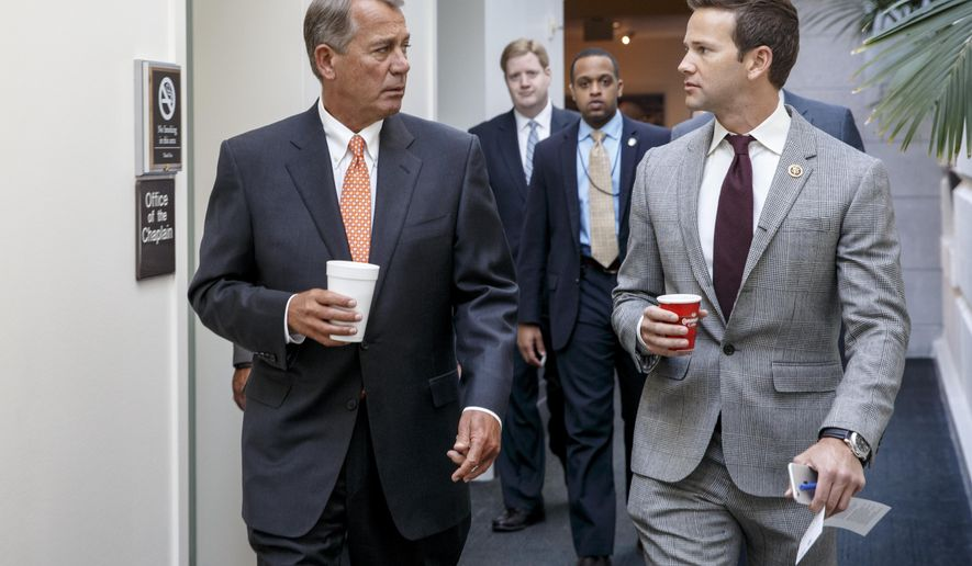 """FILE - In this Jan. 9, 2015, file photo, House Speaker John Boehner of Ohio, left, walks with Rep. Aaron Schock, R-Ill., on Capitol Hill in Washington. Schock, who decorated his office in a style modeled after the TV show """"Downton Abbey"""" may face an ethics investigation. A watchdog group has asked a congressional review panel to examine whether Schock broke House rules by accepting professional interior design work for free.(AP Photo/J. Scott Applewhite, File)"""