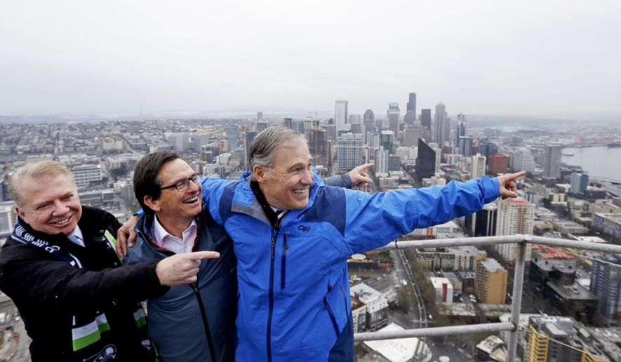 """Gov. Jay Inslee, right, Space Needle Chairman Jeff Wright, center, and Seattle Mayor Ed Murray playfully pose and point south toward San Francisco, indicating their belief that the Seattle Seahawks will be in the Super Bowl there next year, after the three raised a new """"Thank You Seahawks,"""" flag atop the Space Needle Wednesday, Feb. 4, 2015, in Seattle. Before the new flag was raised today, the Space Needle sported the Seahawks """"12th Man"""" flag during their Super Bowl run. (AP Photo/Elaine Thompson)"""