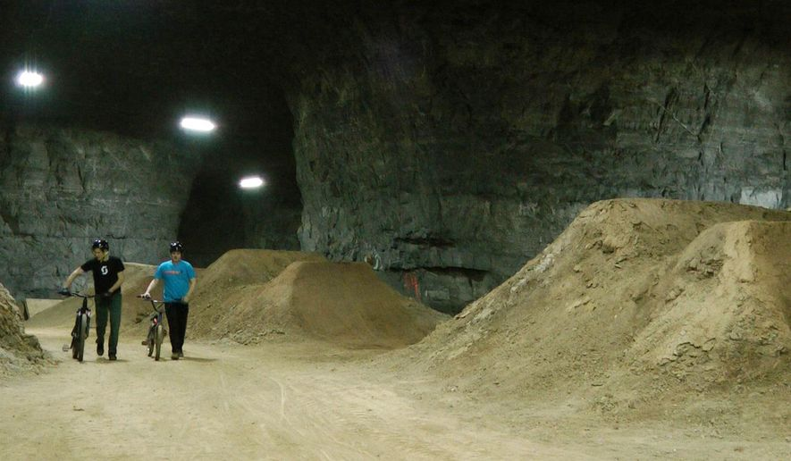 In this Jan. 21, 2015 photo, bike riders Brad Titzer, left, and Derek Fetko walk their bikes during a test run through a new underground bike park in Louisville, KY. The course is built inside an old limestone mine that has become a tourist attraction in Louisville in recent years. (AP Photo/Dylan Lovan)